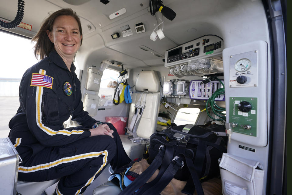 Air ambulance flight paramedic, Rita Krenz, poses inside the helicopter that she works in Weyers Cave, Va., Monday, March 15, 2021. Krenz started a fund-raising campaign that brought in more than $18,000 for the charity that has helped RIP Medical Debt forgive the debt of more than 900 people so far. (AP Photo/Steve Helber)