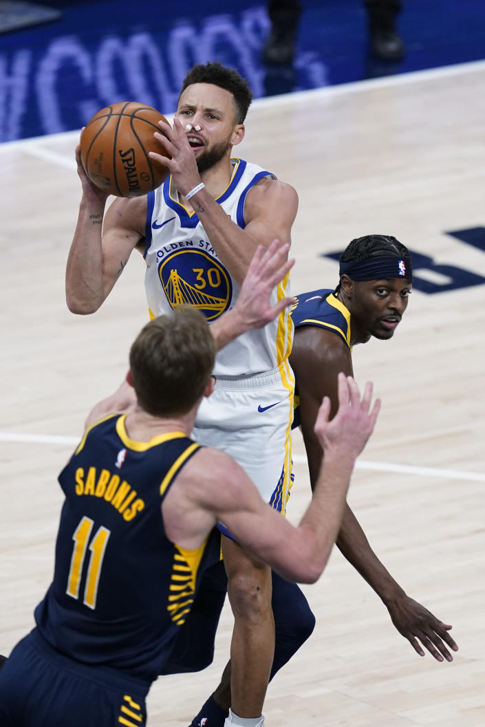 Golden State Warriors' Stephen Curry (30) shoots from between Indiana Pacers' Justin Holiday, right, and Domantas Sabonis during the second half of an NBA basketball game Wednesday, Feb. 24, 2021, in Indianapolis. (AP Photo/Darron Cummings)