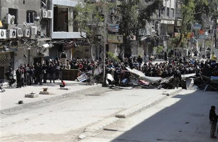 Residents wait to receive food aid distributed by Al-Wafaa campaign at the Palestinian refugee camp of Yarmouk, south of Damascus April 1, 2014. REUTERS/Rame Alsayed