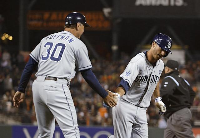 San Diego Padres' Tommy Medica, right, is greeted by third base coach Glenn Hoffman after hitting a home run off San Francisco Giants relief pitcher Javier Lopez in the eighth inning of a baseball game Tuesday, June 24, 2014, in San Francisco. (AP Photo/Eric Risberg)