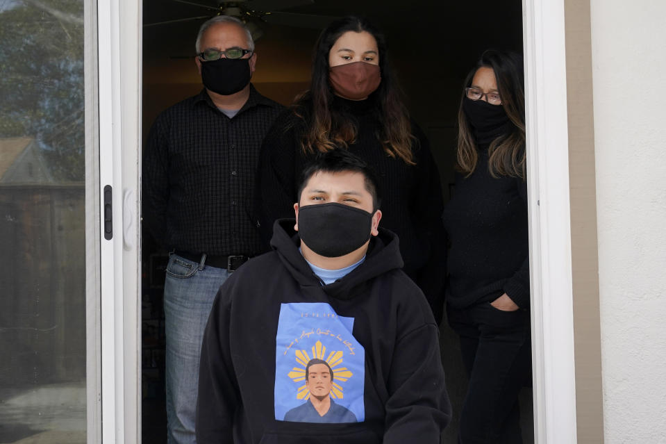 Andrei Quinto, foreground, wears a shirt with an image of his brother, Angelo Quinto, while posing for photos with Robert Collins, from top left, Bella Collins and Cassandra Quinto-Collins during an interview in Antioch, Calif., Tuesday, March 16, 2021. Angelo Quinto died three days after being restrained on Dec. 23, 2020, in police custody while having a mental health crisis. Lawmakers in several states are proposing legislation that would require more training for police in how to interact with someone in a mental crisis following some high-profile deaths. (AP Photo/Jeff Chiu)