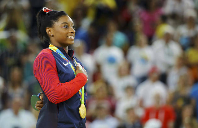 <p>Simone Biles of USA sings her national anthem with her gold medal on the podium after the women's vault victory ceremony at the Rio Olympics on August 14, 2016. (REUTERS/Mike Blake) </p>