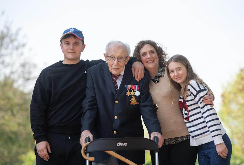 File photo dated 16/04/2020 of the then 99-year-old war veteran Captain Tom Moore, with (left to right) grandson Benji, daughter Hannah Ingram-Moore and granddaughter Georgia, at his home in Marston Moretaine, Bedfordshire, after he achieved his goal of 100 laps of his garden. Captain Sir Tom Moore has died at the age of 100 after testing positive for Covid-19, his daughters Hannah and Lucy said in a statement. Issue date: Tuesday February 2, 2021.