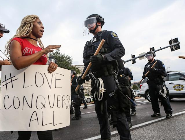 <p>A woman says a prayer next to a police officer during protests after the not guilty verdict in the murder trial of Jason Stockley, a former St. Louis police officer charged with the 2011 shooting of Anthony Lamar Smith, in St. Louis, Mo., Sept. 17, 2017. (Photo: Lawrence Bryant/Reuters) </p>