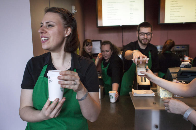 Starbucks baristas serve coffee during the company's annual shareholder's meeting in Seattle, Washington March 18, 2015. REUTERS/David Ryder (UNITED STATES - Tags: BUSINESS)