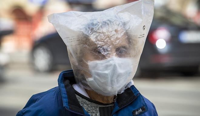 A woman wears a face mask and plastic bag over her head in the Czech Republic. Photo: Kateøina