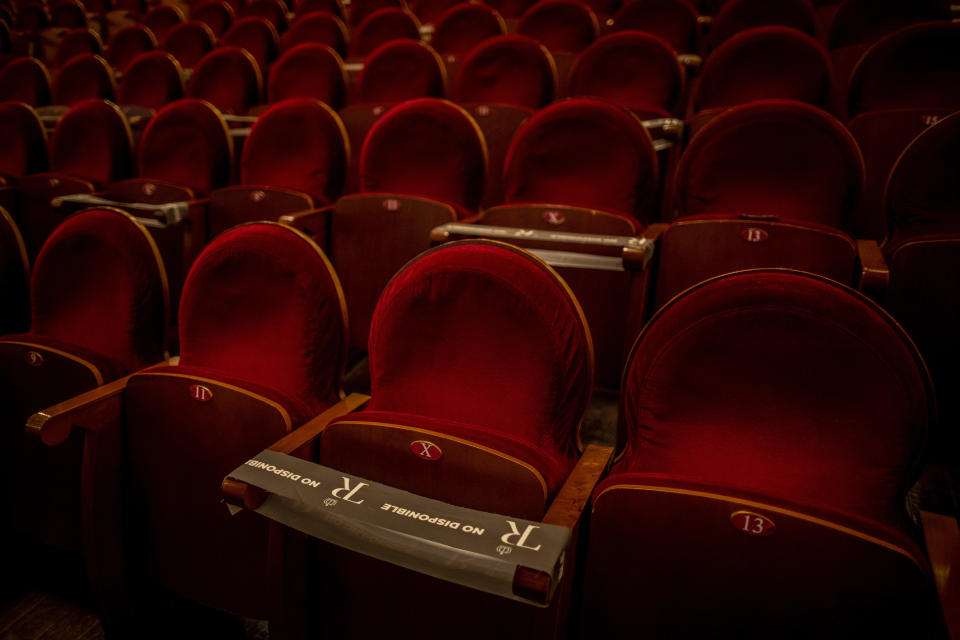 "A ribbon saying ""not available"" covers seats on Thursday, Nov. 12, 2020, at the Teatro Real in Madrid, Spain, to help the audience maintain social distancing. The opera house is again open, although to smaller audiences, during the coronavirus pandemic. (AP Photo/Bernat Armangue)"