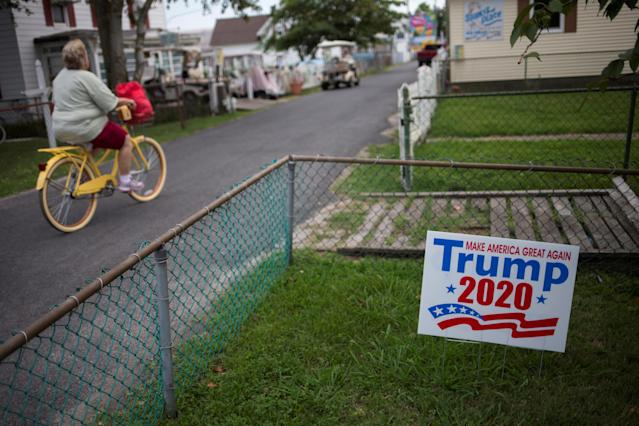 <p>A woman cycles past a house displaying a sign supporting U.S. President Donald Trump on Tangier Island, Virginia, Aug. 2, 2017. (Photo: Adrees Latif/Reuters) </p>