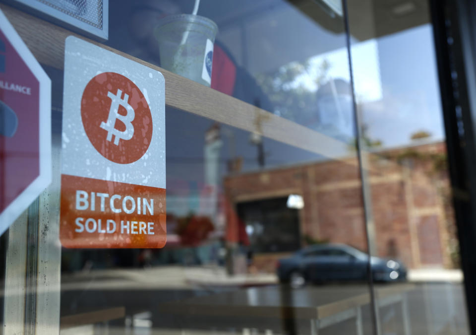 A bitcoin sticker is seen in the window of Locali Conscious Convenience store, in Venice, Los Angeles, California. Photo; Lucy Nicholson/Reuters