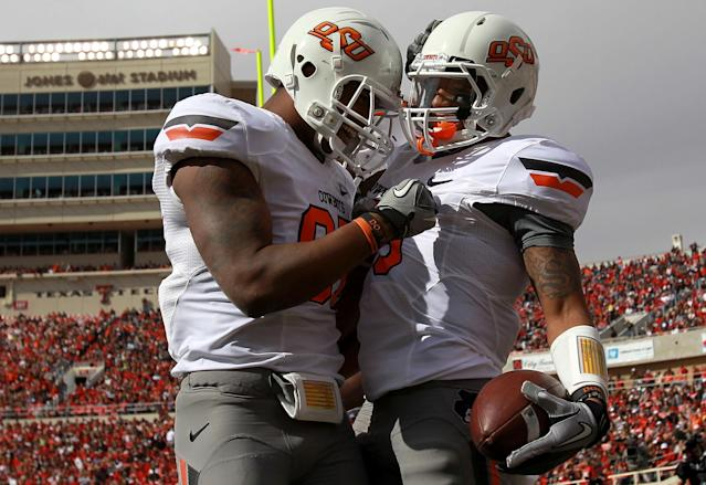 LUBBOCK, TX - NOVEMBER 12: (R-L) Josh Stewart #5 of the Oklahoma State Cowboys and Tracy Moore #87 celebrate a touchdown against the Texas Tech Red Raiders at Jones AT&T Stadium on November 12, 2011 in Lubbock, Texas. (Photo by Ronald Martinez/Getty Images)
