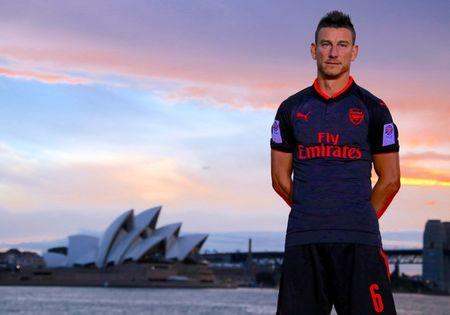 Soccer player Laurent Koscielny from English Premier League club Arsenal wears the 'Third Kit' for the 2017/2018 season as he stands in front of the Sydney Opera House in Sydney Harbour, Australia, July 12, 2017.  REUTERS/David Gray