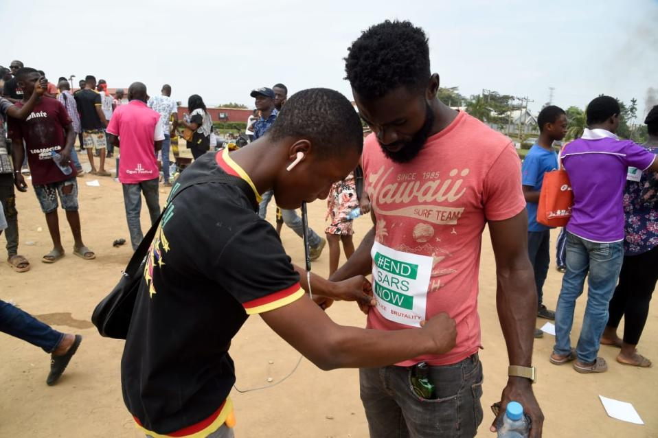 "<div class=""inline-image__caption""><p>A man pastes a sticker on a fellow protester that reads ""END SARS NOW"" along the Lagos -Ibadan expressway during a demonstration to press for the scrapping of Special Ant-Robbery Squad (SARS) on October 19, 2020. At least 15 people were killed, including two policemen, since protests against police brutality erupted in Nigeria this month, according to Amnesty International.</p></div> <div class=""inline-image__credit"">PIUS UTOMI EKPEI/AFP via Getty Images</div>"