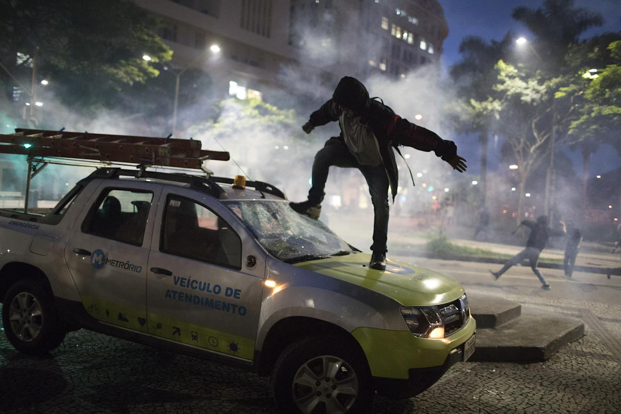 <p>A demonstrator breaks the windshield of a truck that belongs to a subway maintenance crew after clashes with police broke out during a general strike in Rio de Janeiro, Brazil, Friday, April 28, 2017. Public transport largely came to a halt across much of Brazil on Friday and protesters blocked roads and scuffled with police as part of a general strike to protest proposed changes to labor laws and the pension system. (AP Photo/Leo Correo) </p>