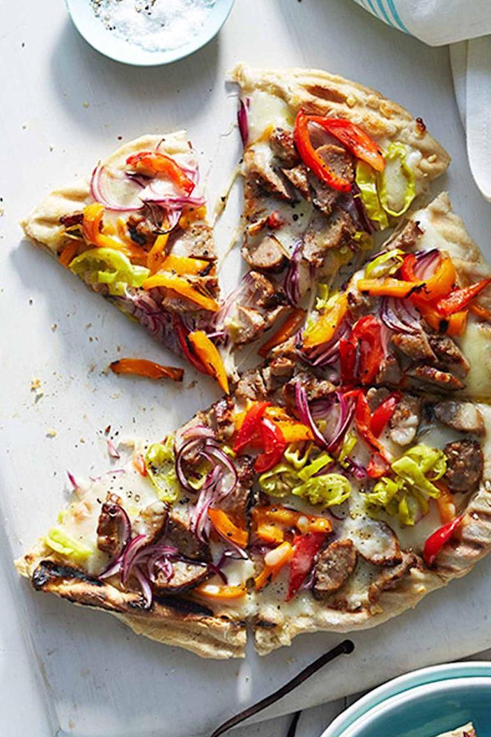 """<p>Grilling this homemade pizza, topped with sweet Italian sausage and two kinds of peppers, is a deliciously unexpected way to finish this classic, picnic-friendly dinner.</p><p><a href=""""https://www.womansday.com/food-recipes/food-drinks/recipes/a12514/grilled-sausage-pepper-pizza-recipe-wdy0614/"""" rel=""""nofollow noopener"""" target=""""_blank"""" data-ylk=""""slk:Get the recipe for Grilled Sausage and Pepper Pizza."""" class=""""link rapid-noclick-resp""""><u><em>Get the recipe for Grilled Sausage and Pepper Pizza.</em></u></a></p>"""