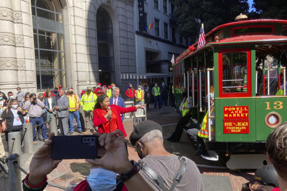 Mayor London Breed welcomes people to return of the cable car service during a ceremony at the Powell Street turnaround plaza in San Francisco on Monday, Aug. 2, 2021. San Francisco's iconic cable cars are rolling again after being sidelined by the pandemic for months. People were already forming long lines to ride the cable cars, which will offer free rides the month of August. (AP Photo/Olga Rodriguez)