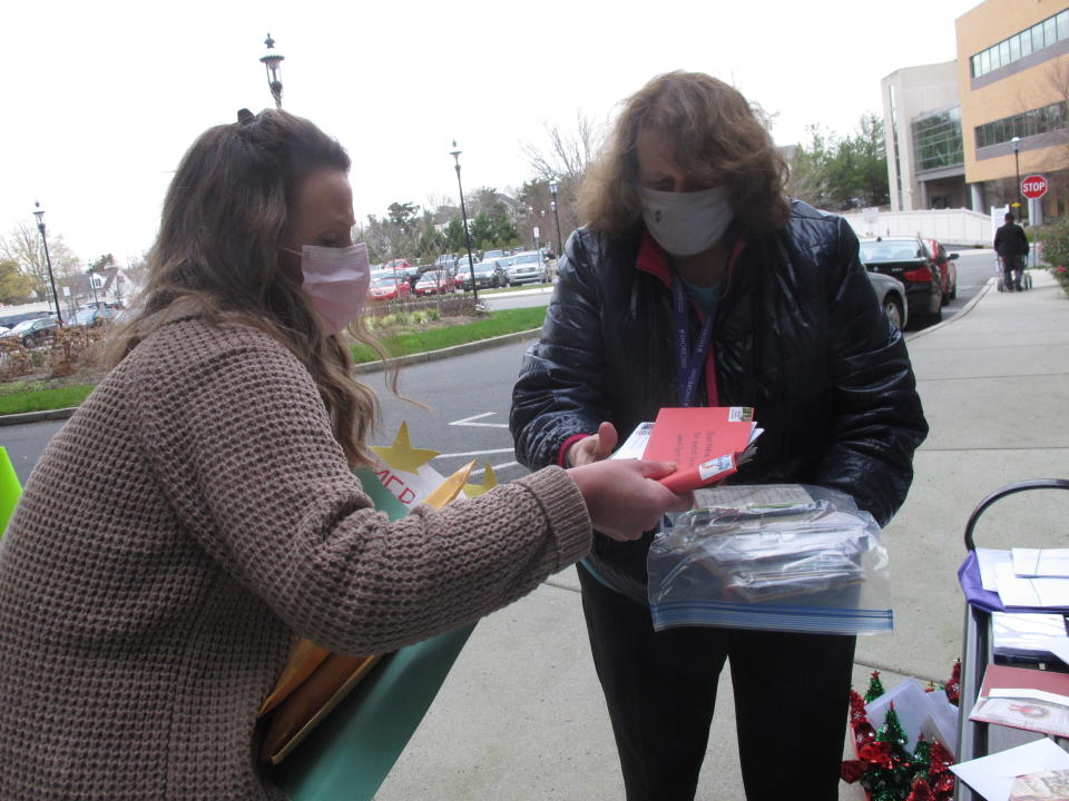 Kathleen Schallus, left, and Suzanne Marino, right, sort through holiday cards sent to Shore Medical Center in Somers Point, N.J. on Dec. 8, 2020. Because most hospitals won't allow visitors during the coronavirus pandemic, hospitals across the country are asking people to make or buy cards to be given to patients as the holidays approach. (AP Photo/Wayne Parry)
