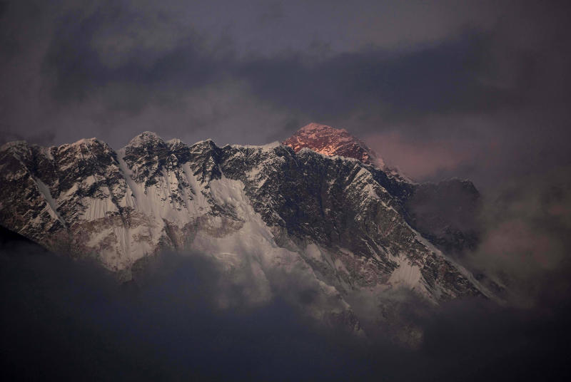 """FILE – In this Oct. 27, 2011 file photo, the last light of the day sets on Mount Everest as it rises behind Mount Nuptse as seen from Tengboche, in the Himalaya's Khumbu region, Nepal. The Everest climbing season began March 2014 with new rules that require climbers to bring down at least eight kilograms (17.6 pounds) of their personal garbage, and more security officials at the mountain's base camp to help climbers. More than 4,000 climbers have scaled the 8,850-meter (29,035-foot) summit since it was conquered in 1953 by Edmund Hillary and his Sherpa guide Tenzing Norgay. Over the years, climbers have left tons of garbage on the slopes on the mountain, and some have called it the """"world's highest garbage dump."""" (AP Photo/Kevin Frayer, File)"""