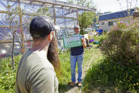 Melynda Small holds up a sign for the Landscaping With Love greenhouse in Otis, Ore., on Thursday, May. 13, 2020. The greenhouse provides landscaping materials free to residents, helping the small town on the Oregon coast recover from the devastating fire that destroyed 293 homes. (AP Photo/Craig Mitchelldyer)