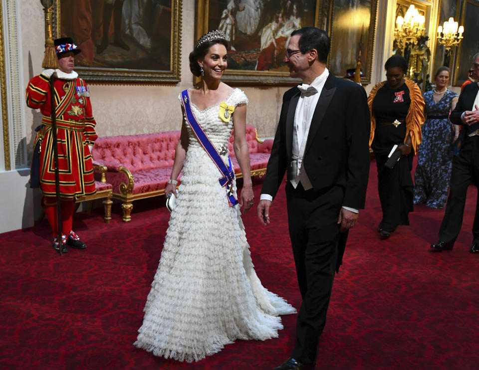 FILE - In this Monday, June 3, 2019 file photo, Kate, the Duchess of Cambridge and United States Secretary of the Treasury, Steven Mnuchin arrive through the East Gallery ahead of the State Banquet at Buckingham Palace in London. US President Donald Trump is on a three-day state visit to Britain. Prince Philip was the longest serving royal consort in British history. In Britain, the husband or wife of the monarch is known as consort, a position that carries immense prestige but has no constitutional role. The wife of King George VI, who outlived him by 50 years, was loved as the Queen Mother. Prince Charles' wife, Camilla, has worked to emerge from the shadow of his immensely popular first wife, Diana. (Victoria Jones/Pool Photo via AP, File)