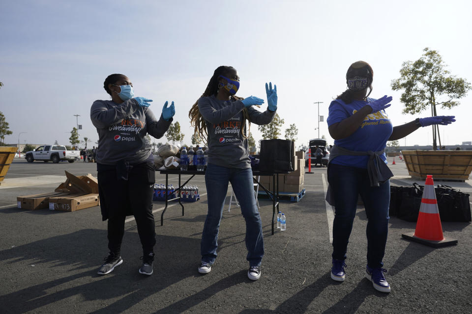 Volunteers dance while waiting to distribute food at SoFi Stadium ahead of Thanksgiving and amid the COVID-19 pandemic, Monday, Nov. 23, 2020, in Inglewood, Calif. (AP Photo/Marcio Jose Sanchez)