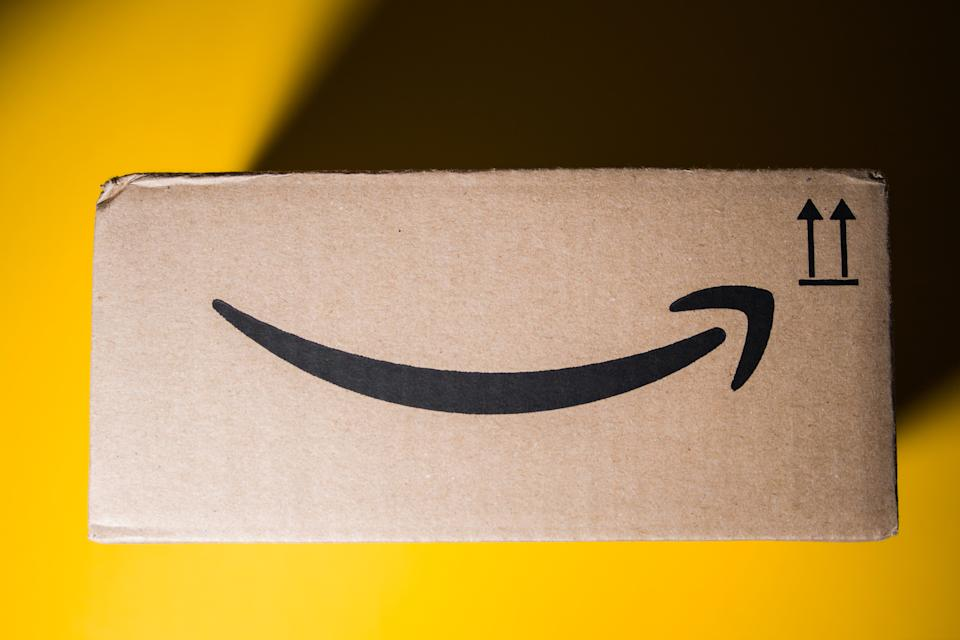 PARIS, FRANCE - SEP 28, 2018: Directly above view of New Amazon Cardboard box against yellow background. Amazon Prime is the online paid subscription service offered by Amazon.com web-commerce site