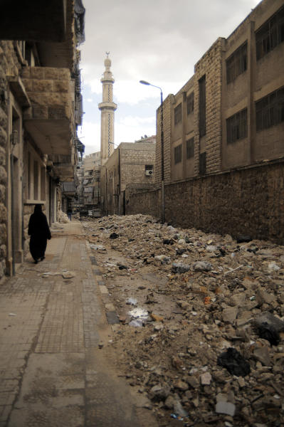 In this Saturday, Nov. 10, 2012 photo, a women passes near rubble and garbage in the Al-Bohout area of Aleppo, Syria. Due the heavy fighting and shelling, the garbage collection system collapsed weeks ago. (AP Photo/Mónica G. Prieto)