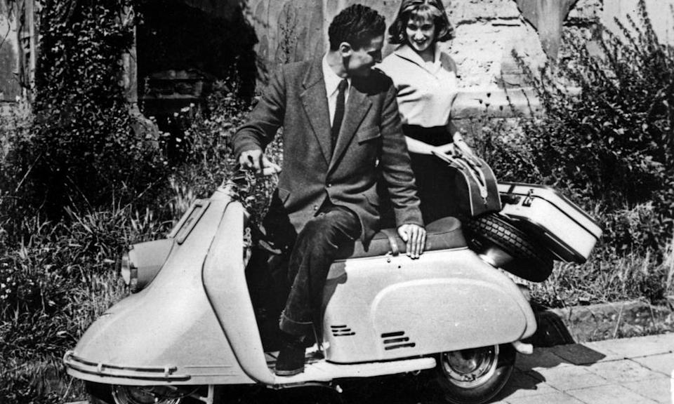 A couple on a Heinkel Tourist 103 A0 motor scooter, 1955 - 1957, with an unwheeled suitcase on the back.