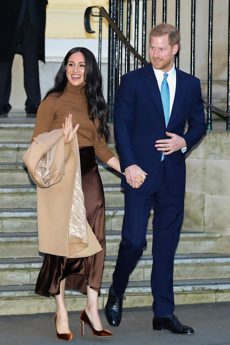 Meghan Markle in a brown outfit and Prince Harry in a blue suit at Clarence House