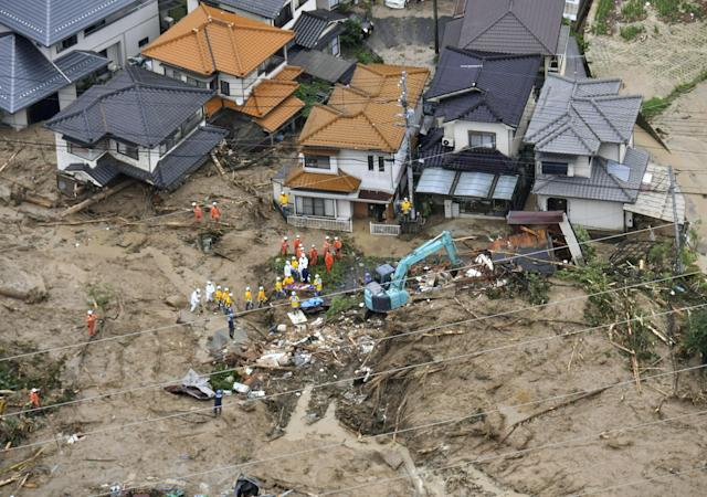 <p>Rescue workers are seen next to houses damaged by a landslide following heavy rain in Hiroshima, western Japan, in this photo taken by Kyodo July 7, 2018. (Photo: Kyodo via Reuters) </p>
