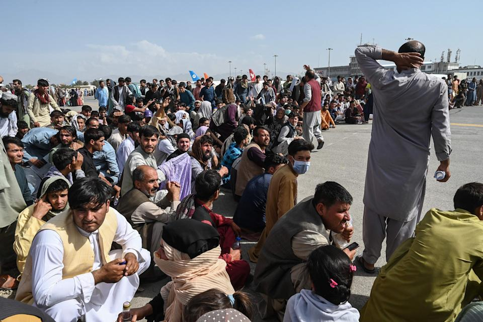 TOPSHOT - Afghan passengers sit as they wait to leave the Kabul airport in Kabul on August 16, 2021, after a stunningly swift end to Afghanistan's 20-year war, as thousands of people mobbed the city's airport trying to flee the group's feared hardline brand of Islamist rule. (Photo by Wakil Kohsar / AFP) (Photo by WAKIL KOHSAR/AFP via Getty Images)