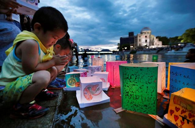<p>Children pray after releasing paper lanterns on the Motoyasu river facing the Atomic Bomb Dome in remembrance of atomic bomb victims on the 72nd anniversary of the bombing of Hiroshima, western Japan, Aug. 6, 2017, in this photo taken by Kyodo. (Photo: Kyodo via Reuters) </p>