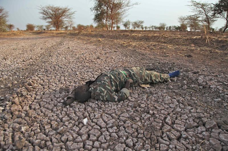 This photo of Saturday, April 14, 2012, shows a dead Sudanese soldier lying on the road to the Heglig front lines in South Sudan as fighting between Sudan and South Sudan over the past two weeks  centered around the oil-rich Heglig area.  Two Sudanese Sukhoi fighters dropped 6 bombs in the Bentiu area, killing five and wounding four others. (AP Photo/Michael Onyiego)