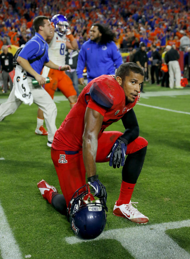 Arizona running back Austin Hill watches from the field after the Fiesta Bowl NCAA college football game against Boise State, Wednesday, Dec. 31, 2014, in Glendale, Ariz. Boise State won 38-30. (AP Photo/Rick Scuteri)