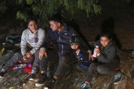 A family from Honduras sits on the ground after they were smuggled on an inflatable raft across the Rio Grande, in Roma, Texas Saturday, March 27, 2021. Roma, a town of 10,000 people with historic buildings and boarded-up storefronts in Texas' Rio Grande Valley, is the latest epicenter of illegal crossings, where growing numbers of families and children are entering the United States to seek asylum. (AP Photo/Dario Lopez-Mills)
