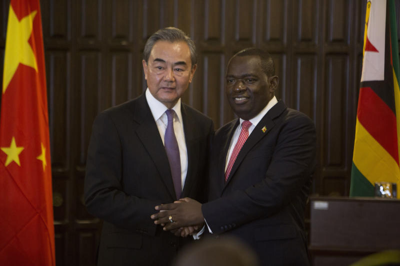 China's Foreign Minister Wangi Yi, left, greets Zimbabwe's Foreign Minister Sibusiso Moyo after a joint press conference in Harare, Zimbabwe, Sunday, Jan, 12, 2020.  Wangi Yi is in Zimbabwe as part of a five nation tour of Africa that seeks to promote the Asian economic and political interests on the continent. (AP Photo/Tsvangirayi Mukwazhi)