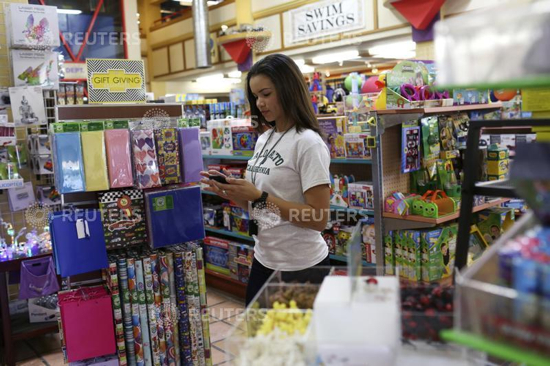Store employee Ashley Beal takes an order via a smartphone app to be delivered to the customer by a Google car and courier at a toy and sporting goods shop in Palo Alto, California