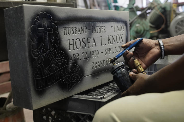 Leon Brown, long-time assistant to Hosea Knox, owner of Elmo's Tombstone Service, spray paints the lettering on the tombstone for the recently-deceased Knox, on the South Side of Chicago, Tuesday, Sept. 14, 2021, one day after Knox's funeral. (AP Photo/Charles Rex Arbogast)