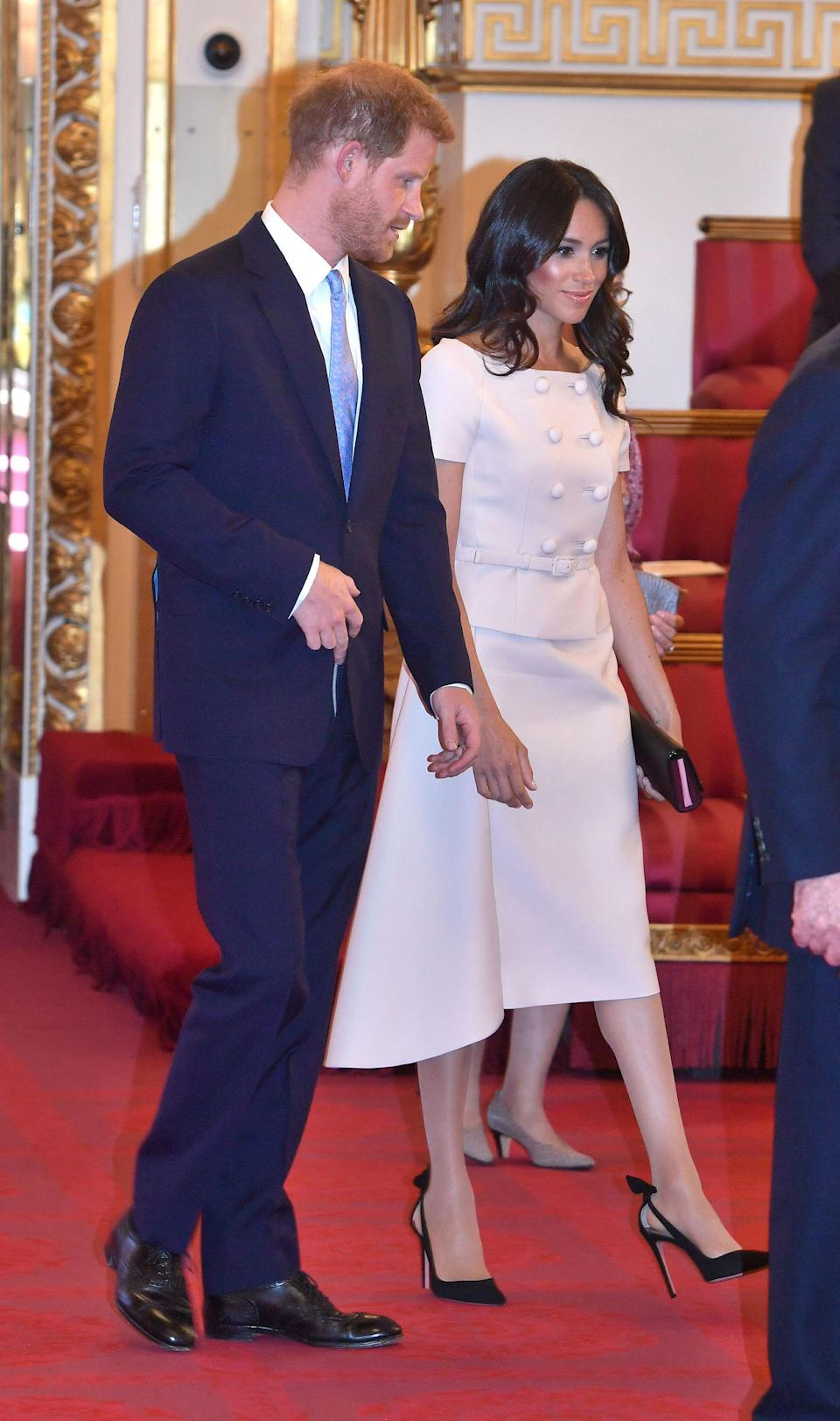 For the Queen's Young Leaders ceremony at Buckingham Palace on 27 June, Meghan opted for a powder pink skirt suit by Prada [Photo: PA]