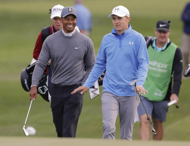Tiger Woods, left, talks with Jordan Spieth as they approach the 17th green during the first round of the Valspar Championship golf tournament Thursday, March 8, 2018, in Palm Harbor, Fla. (AP Photo/Mike Carlson)