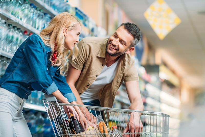 A couple shopping in a warehouse club store smile as they place items in their cart.