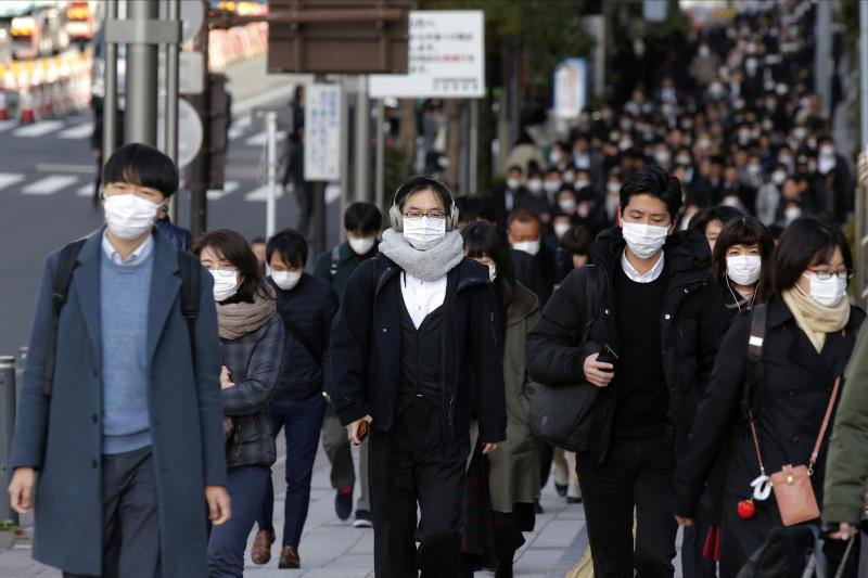 FILE - In this Feb. 20, 2020, photo, people wear masks as they commute during the morning rush hour, in Chuo district in Tokyo. Japan's Prime Minister Shinzo Abe says new measures like companies letting their employees work from home and hospitals expanding their capacity to treat many patients will determine if Japan could control its coronavirus outbreak. (AP Photo/Kiichiro Sato, File)