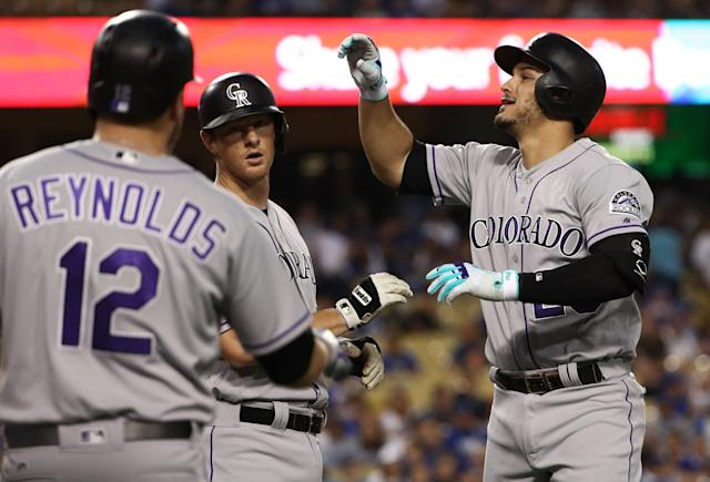 Nolan Arenado #28 of the Colorado Rockies celebrates with DJ LeMahieu #9 as teammate Mark Reynolds #12 looks on after Arenado hit a three-run homerun during the first inning of the MLB game against the Los Angeles Dodgers at Dodger Stadium on September 7, 2017 in Los Angeles, California. (Getty Images)