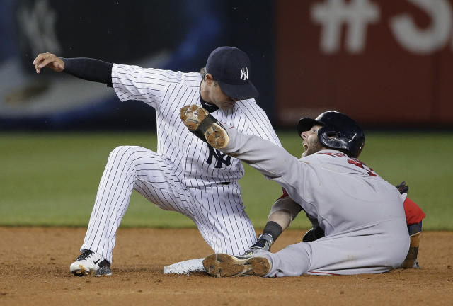 Boston Red Sox's Dustin Pedroia, right, reacts as he slides into second base on a hit to right field as New York Yankees second baseman Brian Roberts applies the tag in the fifth inning of a baseball game, Saturday, June 28, 2014, in New York. Pedroia was initially called safe on the play, but the call was appealed by Yankees manager Joe Girardi and overturned on review. (AP Photo/Julie Jacobson)