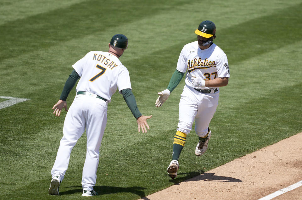Oakland Athletics' Aramis Garcia (37) is congratulated by third base coach Mark Kotsay (7) as he rounds the bases after hitting a two-run home run against the Detroit Tigers during the second inning of a baseball game on Saturday, April 17, 2021, in Oakland, Calif. (AP Photo/Tony Avelar)
