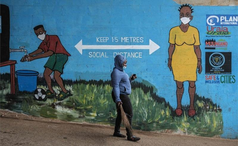 A woman with a facemask walks past graffiti that promotes social distancing.