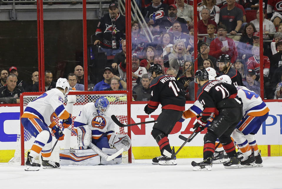 Carolina Hurricanes' Justin Williams (14) scores against New York Islanders goalie Thomas Greiss (1), of Germany, during the second period of Game 4 of an NHL hockey second-round playoff series in Raleigh, N.C., Friday, May 3, 2019. Hurricanes' Nino Niederreiter (21), of the Czech Republic, and Islanders' Anders Lee, left, look on. (AP Photo/Gerry Broome)