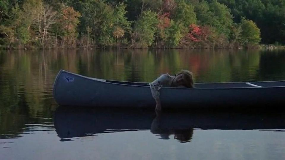 A woman is passed out in a canoe on the lake
