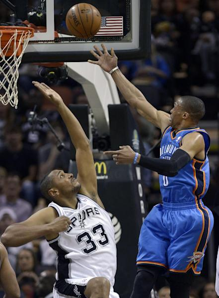 Oklahoma City Thunder's Russell Westbrook, right, shoots over San Antonio Spurs' Boris Diaw, of France, during the first half of an NBA basketball game, Monday, March 11, 2013, in San Antonio. (AP Photo/Darren Abate)
