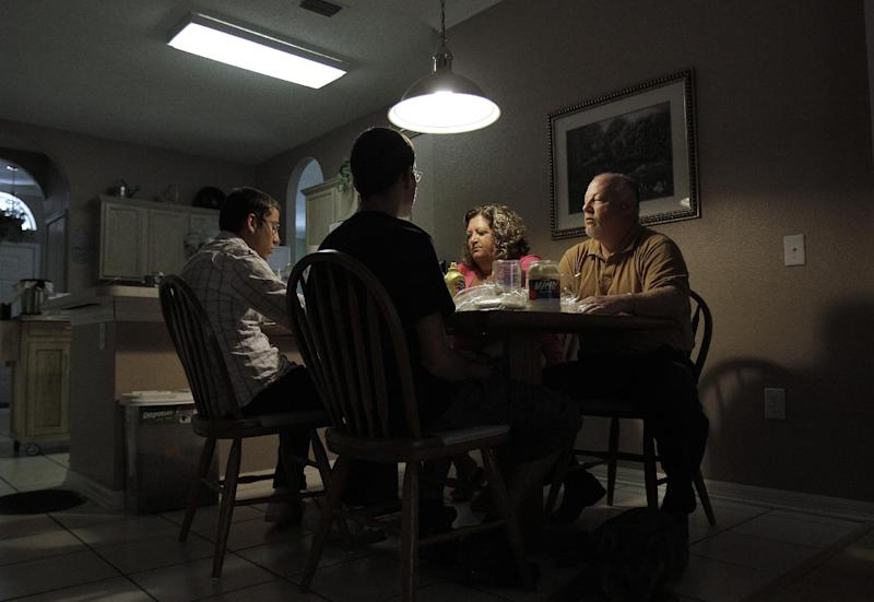 In this July 10, 2011 photo, Deb Carlson, second from right, and her husband Doug, right, have lunch with their adopted sons in Valrico, Fla. The Carlsons' adopted sons have trashed bedrooms, stolen credit cards and threatened to kill them, one drew a disturbing pictures of throwing a party after beheading the southwest Florida couple. While the overwhelming majority of adoptions end happily, some families like the Carlsons say they weren't told about their new child's psychological problems and can't get help from the government agencies that recruited them. (AP Photo/Chris O'Meara)