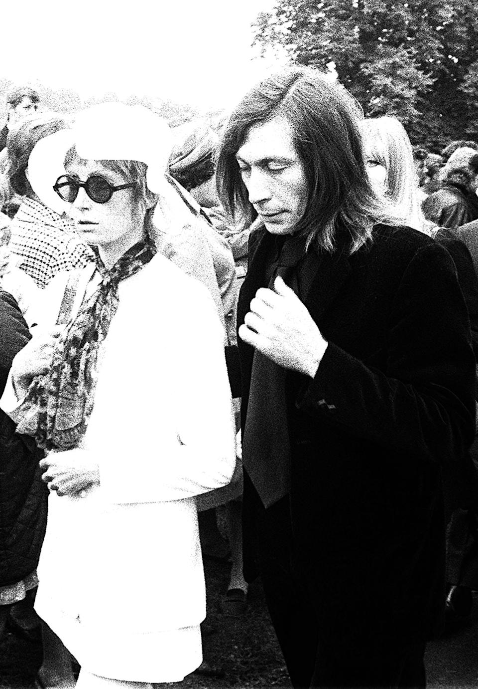 Sad-faced Charlie Watts of the Rolling Stones and his wife Shirley Watts stand at the graveside of Brian Jones. former guitarist with the group, whose funeral took place in Cheltenham., Gloucestershire.   (Photo by PA Images via Getty Images)